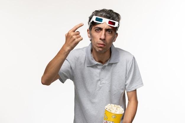 Widok z przodu młody mężczyzna posiadający pakiet popcornu i noszący okulary przeciwsłoneczne d na białej powierzchni