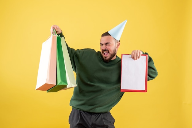 Widok z przodu młody mężczyzna posiadający pakiety zakupów i uwaga na żółtym tle