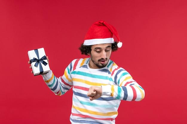 Widok z przodu młody mężczyzna posiadający wakacje obecny na czerwonej ścianie nowy rok wakacje emocje