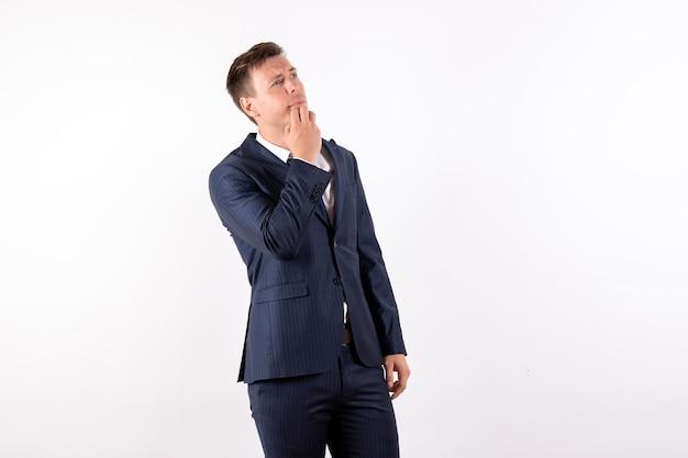 Widok z przodu młody mężczyzna pozuje i myśli w klasycznym surowym garniturze na białym tle