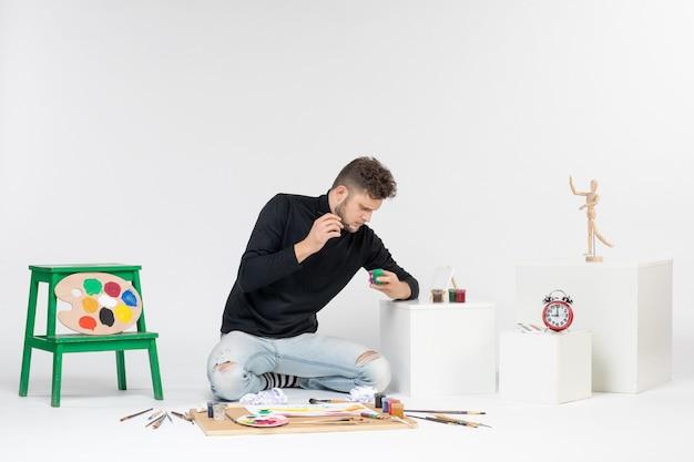 Widok z przodu młody mężczyzna pracujący z farbami na białej ścianie artysta maluje kolory malowania obraz rysuje zdjęcie