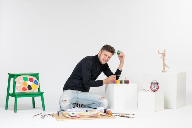 Widok z przodu młody mężczyzna pracujący z farbami na białej ścianie farba sztuka kolor artysta malowanie zdjęć rysowanie zdjęć