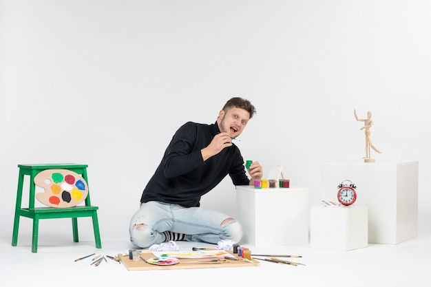 Widok z przodu młody mężczyzna pracujący z farbami na białej ścianie farba sztuka kolor obrazy artysty zdjęcie zdjęcie rysować