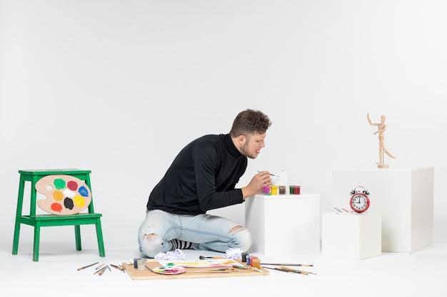 Widok z przodu młody mężczyzna pracujący z farbami na białej ścianie zdjęcie sztuka obraz malarstwo narysuj kolor artysta farba