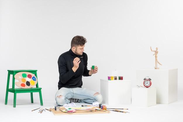 Widok z przodu młody mężczyzna pracujący z farbami na białej ścianie zdjęcie sztuka obraz malarstwo narysuj kolor farby artystyczne