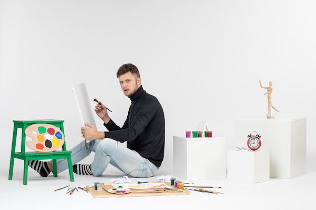 Widok z przodu młody mężczyzna próbujący narysować obraz z pomponem na białej ścianie kolorowy obraz farba artystyczna malowanie rysunkami artysta