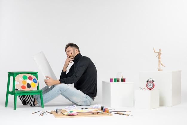 Widok z przodu młody mężczyzna próbuje narysować obraz z pomponem, myśląc na białej ścianie, kolorowy obraz, malowanie, malowanie, rysowanie artysty