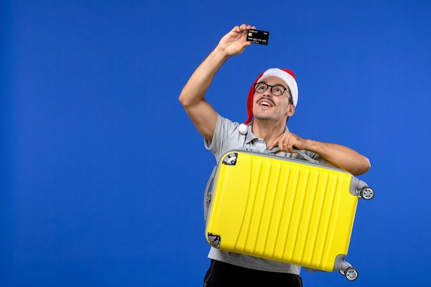 Widok z przodu młody mężczyzna przewożący torbę i kartę bankową na niebieskim biurku samolotu wakacje