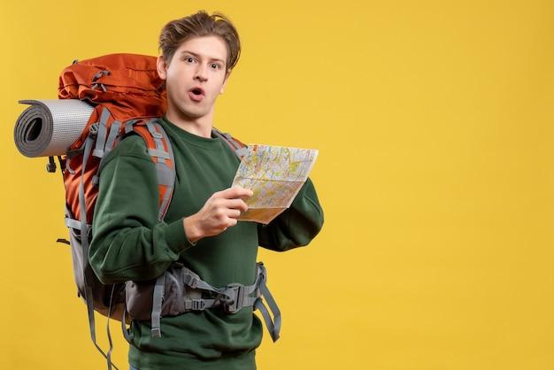 Widok z przodu młody mężczyzna przygotowujący się do wędrówki obserwującej mapę