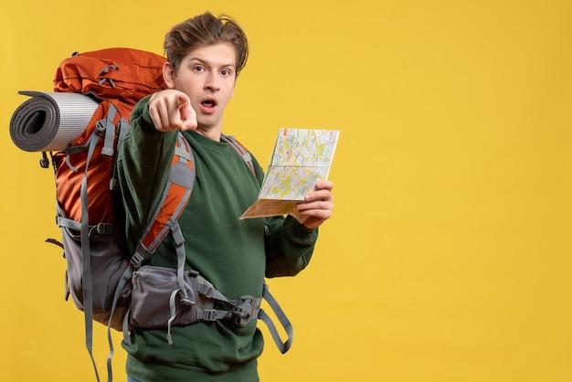 Widok z przodu młody mężczyzna przygotowujący się do wędrówki trzymającej mapę
