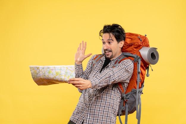 Widok z przodu młody mężczyzna przygotowuje się do turystyki pieszej trzymając mapę na żółto