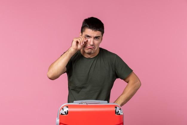 Widok z przodu młody mężczyzna przygotowuje się do wakacji i płacze na różowej przestrzeni