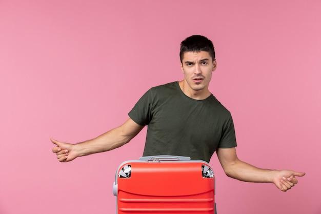 Widok z przodu młody mężczyzna przygotowuje się do wakacji na różowej przestrzeni