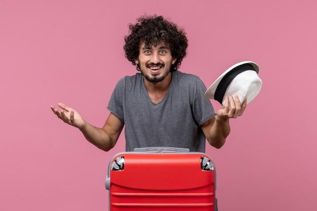 Widok z przodu młody mężczyzna przygotowuje się do wakacji trzymając kapelusz na różowej przestrzeni