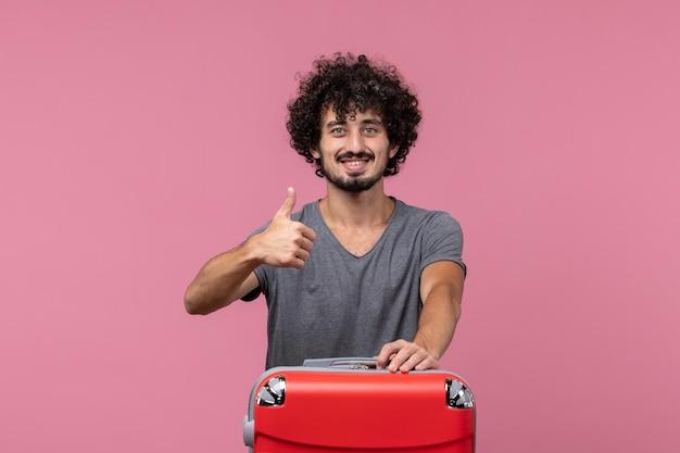 Widok z przodu młody mężczyzna przygotowuje się do wakacji uśmiechając się na różowej przestrzeni