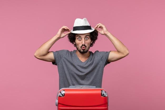 Widok z przodu młody mężczyzna przygotowuje się do wakacji w kapeluszu na jasnoróżowej przestrzeni