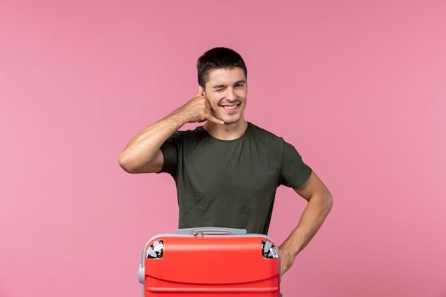 Widok z przodu młody mężczyzna przygotowuje się do wakacji z dużą torbą na różowej przestrzeni
