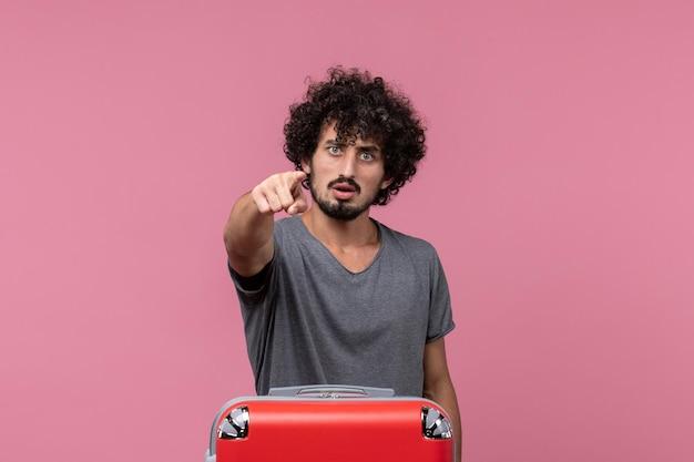 Widok z przodu młody mężczyzna przygotowuje się do wakacji z torbą na różowej przestrzeni