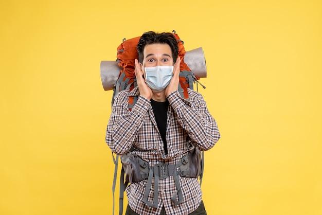 Widok z przodu młody mężczyzna przygotowuje się do wędrówek w masce na żółto