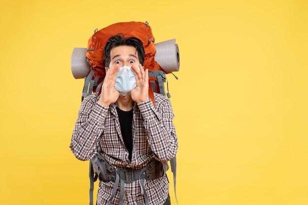 Widok z przodu młody mężczyzna przygotowuje się do wędrówek w masce wzywając na żółto
