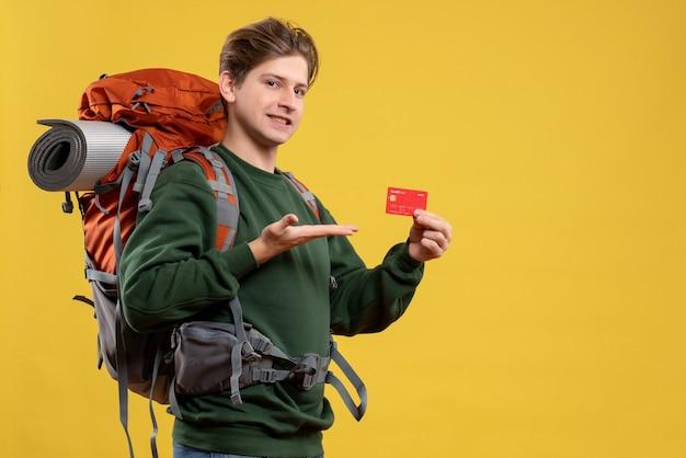 Widok z przodu młody mężczyzna przygotowuje się do wędrówki trzymając czerwoną kartę bankową