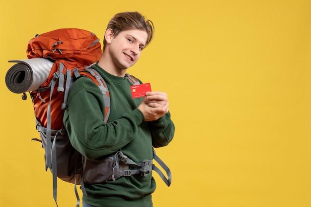 Widok z przodu młody mężczyzna przygotowuje się do wędrówki trzymając kartę bankową