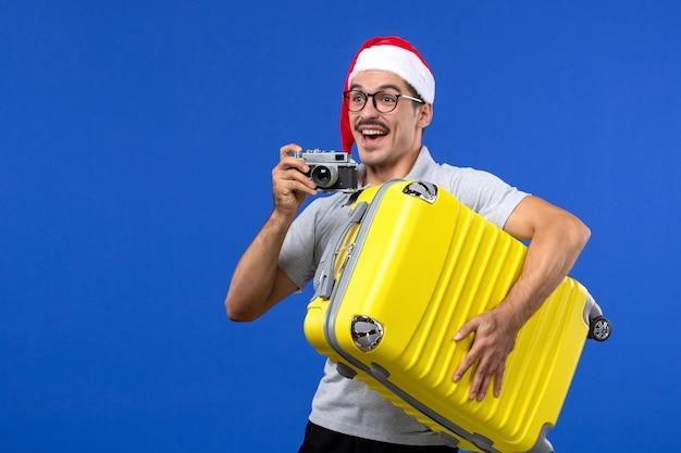 Widok z przodu młody mężczyzna robienie zdjęć aparatem na niebieskiej ścianie loty samolotami wakacyjnymi