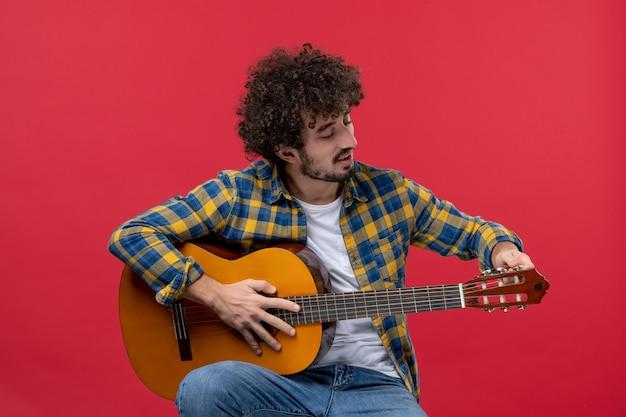 Widok z przodu młody mężczyzna siedzący i grający na gitarze na czerwonej ścianie koncert na żywo muzyka kolor muzyk oklaski grają zespół