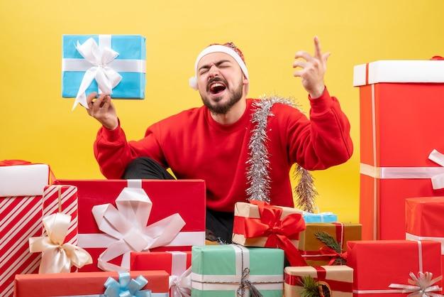 Widok z przodu młody mężczyzna siedzący wokół prezentów i trzymając jeden na żółto