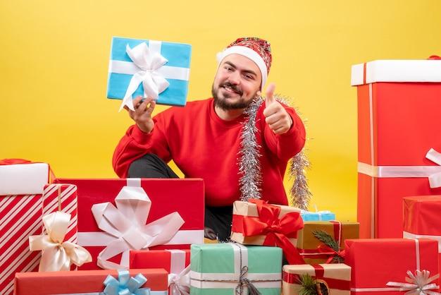 Widok z przodu młody mężczyzna siedzący wokół prezentów i trzymając jeden na żółtym tle
