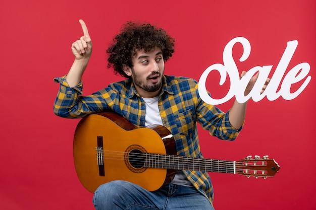 Widok z przodu młody mężczyzna siedzący z gitarą na czerwonej ścianie koncert muzyczny oklaski na żywo muzyk kolor wyprzedaż