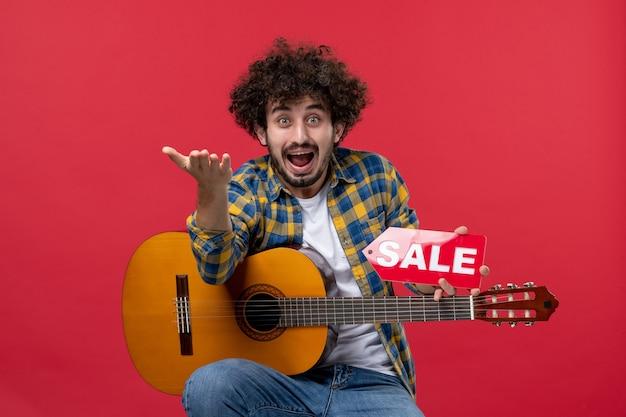 Widok z przodu młody mężczyzna siedzący z gitarą na czerwonej ścianie koncert muzyka na żywo sprzedaż grać muzyka kolor oklaski