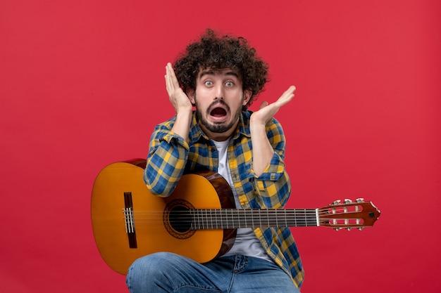 Widok z przodu młody mężczyzna siedzący z gitarą na czerwonej ścianie koncert na żywo muzyka kolor muzyk oklaski grają zespół