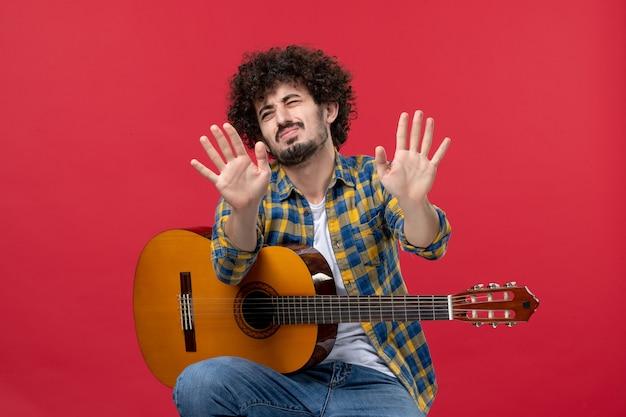 Widok z przodu młody mężczyzna siedzący z gitarą na czerwonej ścianie koncert zespołu oklaski grać muzyka kolor na żywo