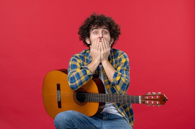 Widok z przodu młody mężczyzna siedzący z gitarą na czerwonej ścianie muzyk zespołu oklaski gra muzykę kolor na żywo