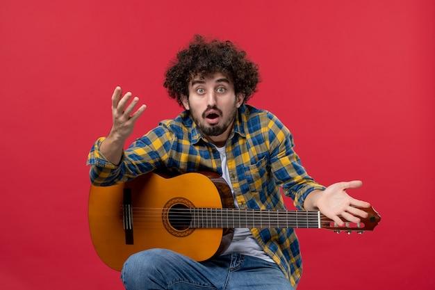 Widok z przodu młody mężczyzna siedzący z gitarą na czerwonej ścianie muzyka wydajność muzyk kolor oklaski zagraj koncert na żywo