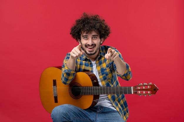 Widok z przodu młody mężczyzna siedzący z gitarą na czerwonej ścianie oklaski koncert muzyk gra muzyka kolor na żywo