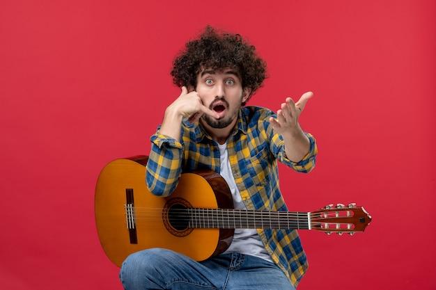 Widok z przodu młody mężczyzna siedzący z gitarą na czerwonej ścianie oklaski zespół koncertowy muzyk grający muzykę na żywo