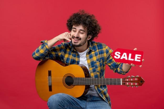 Widok z przodu młody mężczyzna siedzący z gitarą na czerwonej ścianie w kolorze oklaski na żywo muzyk koncert sprzedaż grać