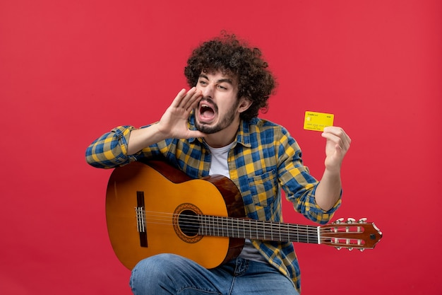 Widok z przodu młody mężczyzna siedzący z gitarą trzymającą kartę bankową na czerwonej ścianie kolor występ koncert oklaski muzyk muzyka na żywo