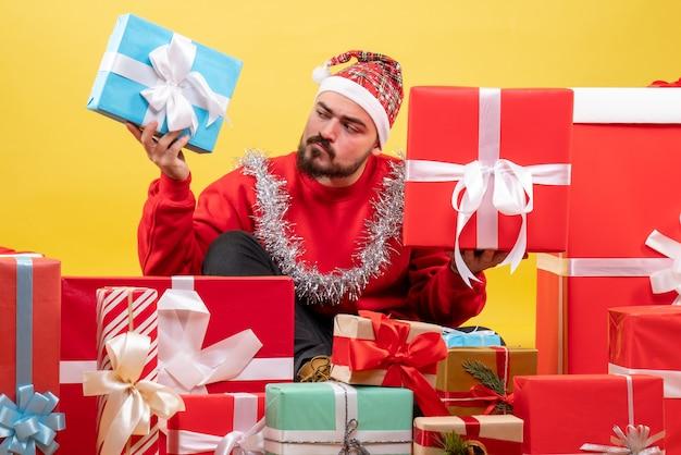 Widok z przodu młody mężczyzna siedzi wokół prezentów świątecznych na żółtym tle