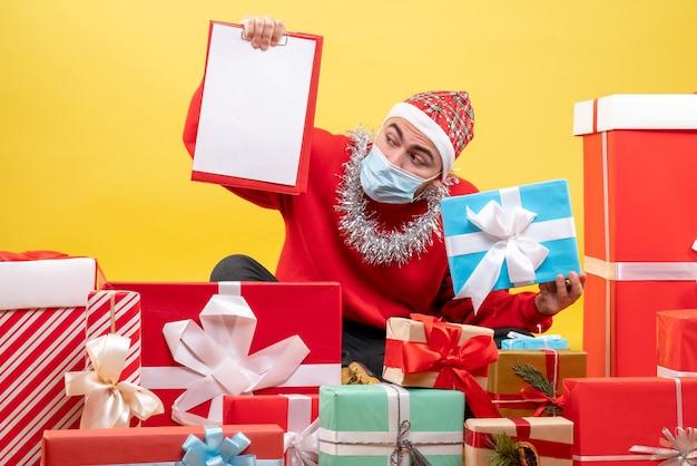 Widok z przodu młody mężczyzna siedzi wokół prezentów świątecznych z notatką na żółtym tle