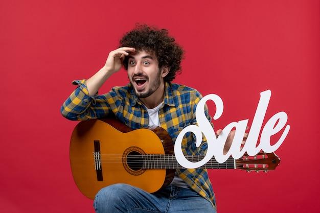 Widok z przodu młody mężczyzna siedzi z gitarą na czerwonej ścianie kolor oklaski muzyk gra koncert zespołu na żywo sprzedaż