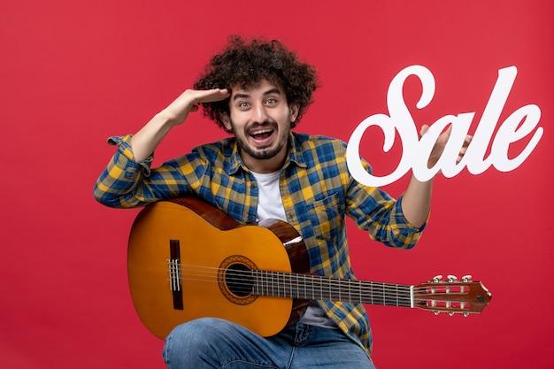 Widok z przodu młody mężczyzna siedzi z gitarą na czerwonej ścianie kolor oklaski muzyk gra zespół koncert muzyka sprzedaż