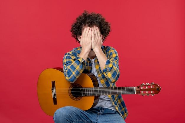 Widok z przodu młody mężczyzna siedzi z gitarą na czerwonej ścianie kolor oklaski muzyk gra zespół koncertowy muzyka na żywo