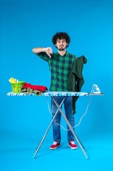 Widok z przodu młody mężczyzna składana zielona koszula na niebieskim tle czysta pralka dom kolor ludzki