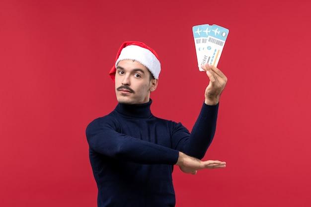 Widok z przodu młody mężczyzna spokojnie trzymając bilety na czerwonym tle