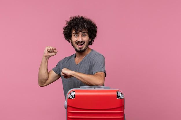 Widok z przodu młody mężczyzna sprawdzający czas z podekscytowanym wyrazem twarzy na różowej przestrzeni