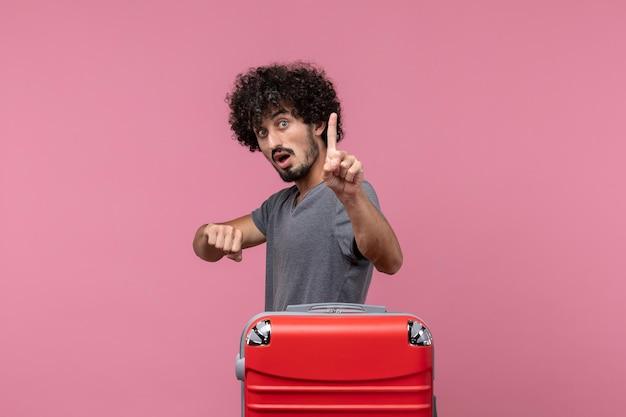 Widok z przodu młody mężczyzna sprawdzający czas z zaskoczonym wyrazem twarzy na różowej przestrzeni