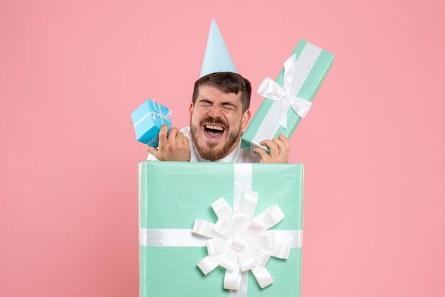 Widok z przodu młody mężczyzna stojący w obecnym pudełku na różowym biurku piżama party zdjęcie emocje sen boże narodzenie